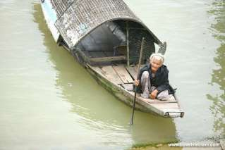 An old woman on a bamboo boat