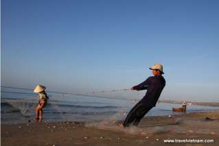 Fishermen pulling fishnet on Mui Ne beach