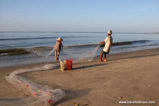 Fishermen pulling fishnet to the shore