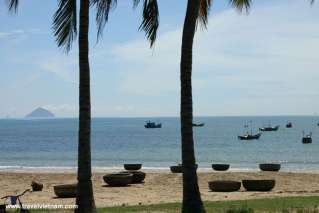Fishing boats and bamboo baskets on beautiful beach in Nha Trang bay
